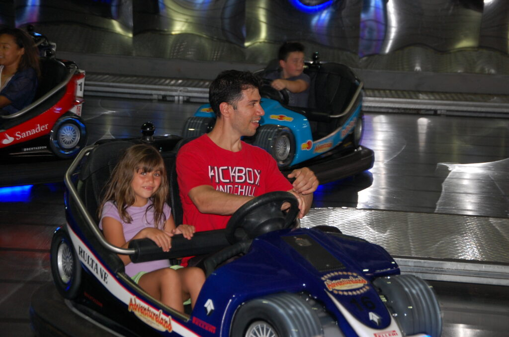 Dad and girl driving a bumper car at Adventureland